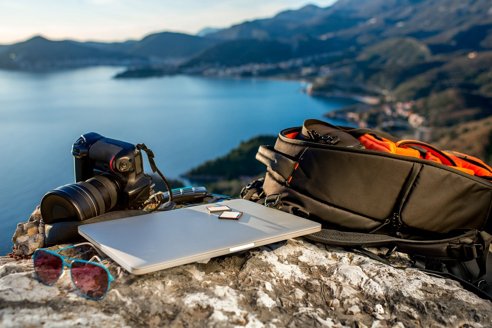 38610814 - travel photographer equipment on rocky mountain with beautiful landscape on the background