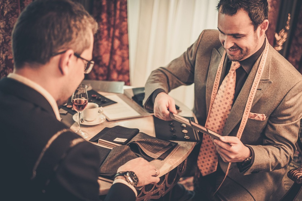 33693217 - tailor and client choosing cloth and buttons for custom made suit