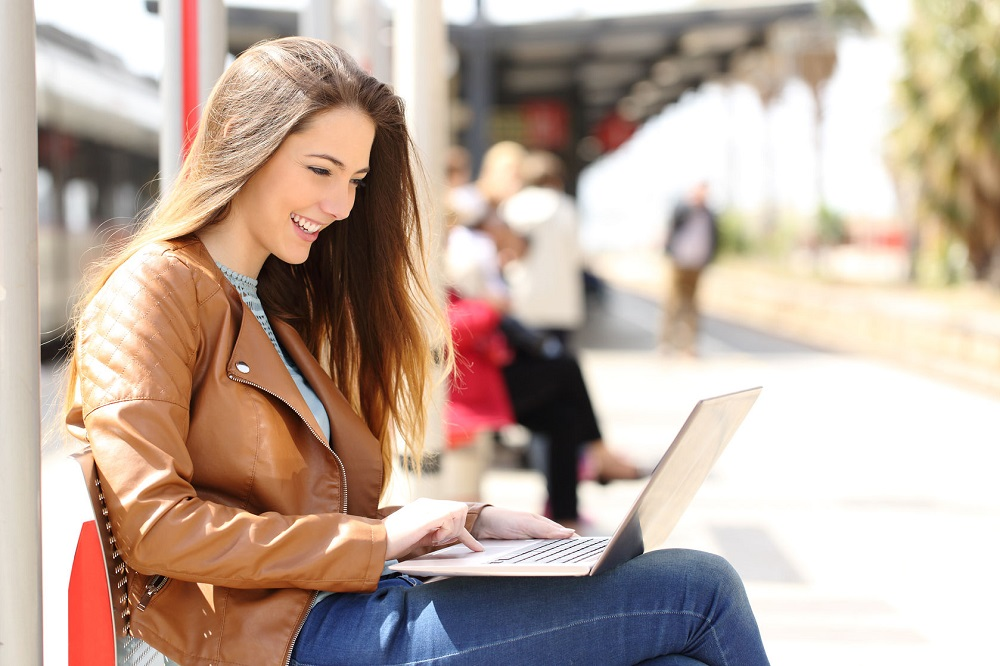 40317203 - side view of a girl using a laptop while waiting in a train station in a sunny day