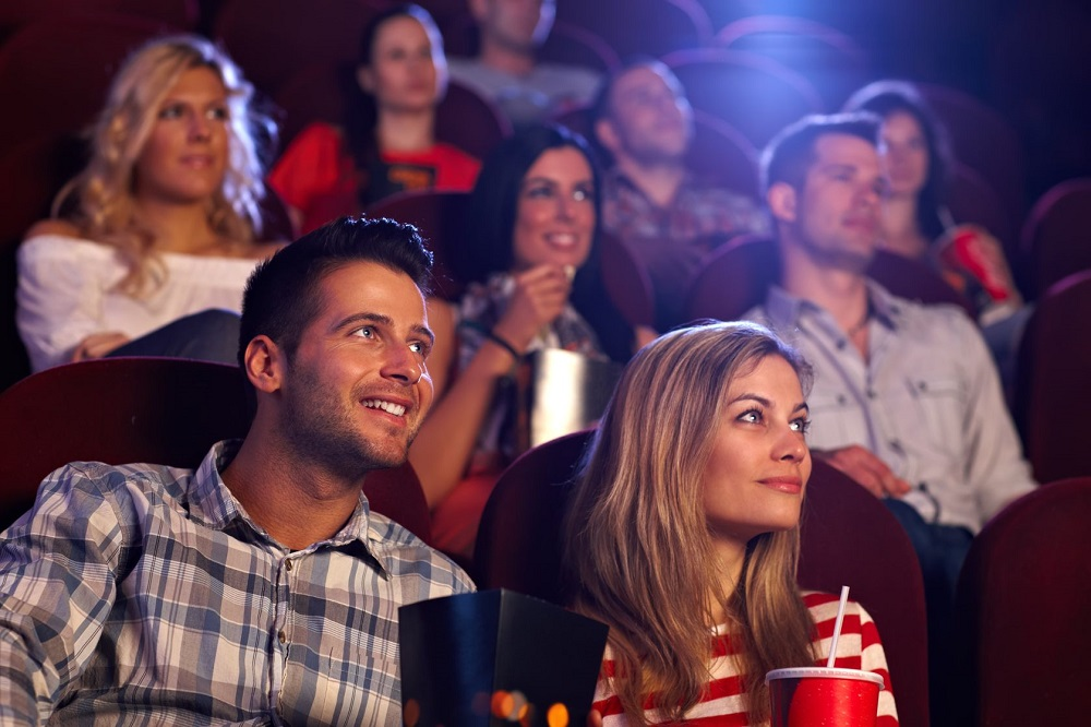 15642376 - young people sitting at auditorium of movie theater, watching movie.