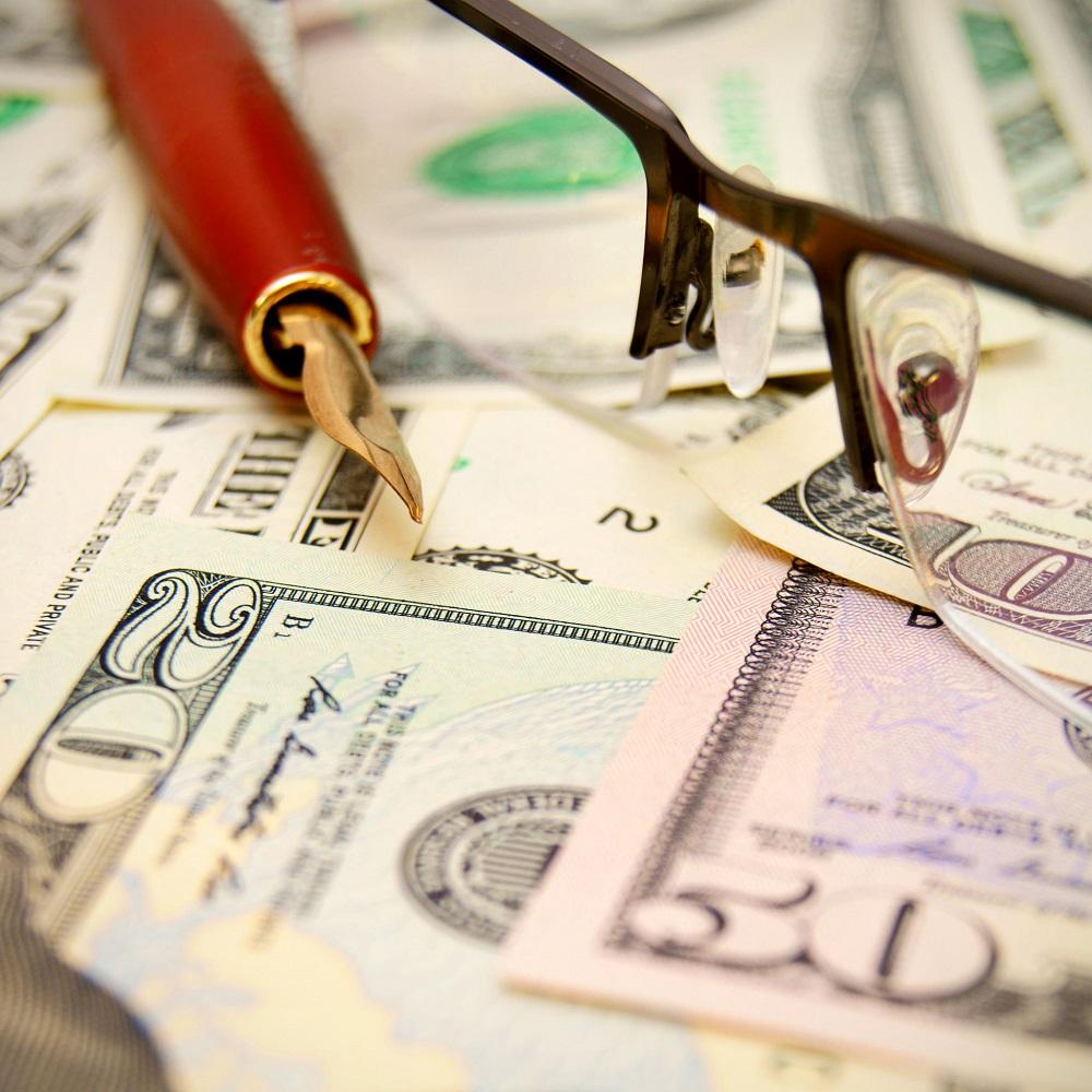22244718 - pen, glasses on dollars.
