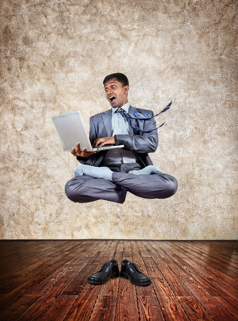 16036603 - levitation by indian businessman with laptop in lotus pose and shoes on the floor at textured background