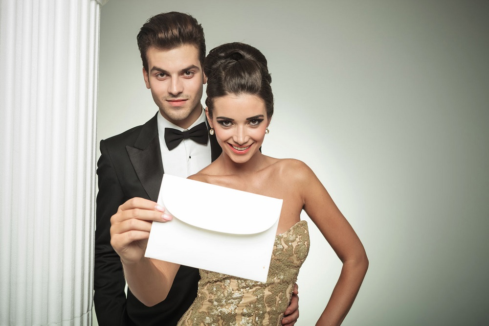 31536176 - happy young couple presenting an invite to their wedding, smiling nar a column in studio