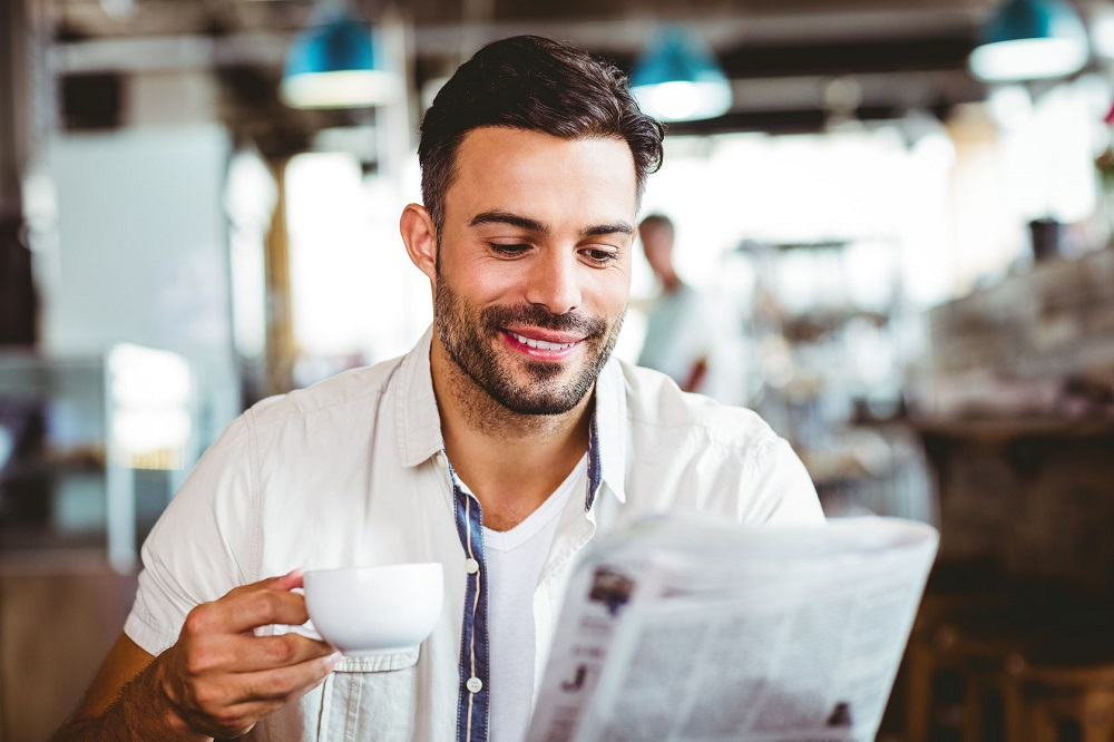 42514915 - young man having cup of coffee reading newspaper at the cafe