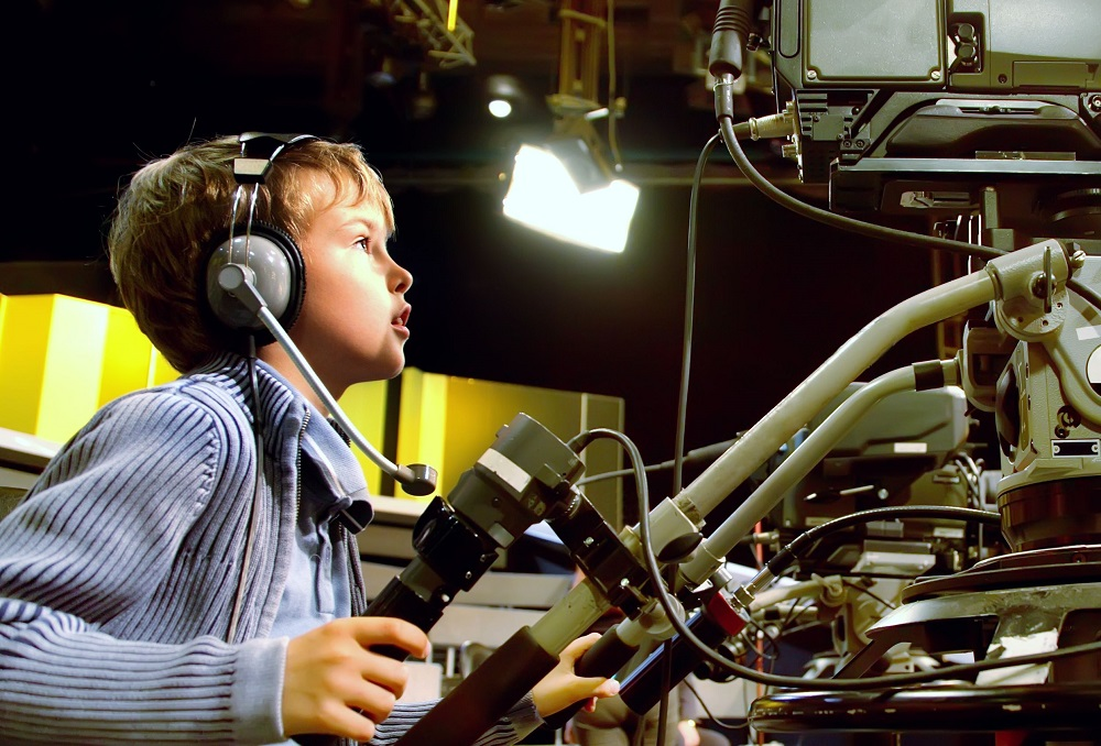 12512710 - little boy with headphones and microphone looks to professional video camera in auditorium on television broadcast